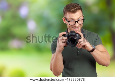 Portrait of a handsome young in glasses man with camera