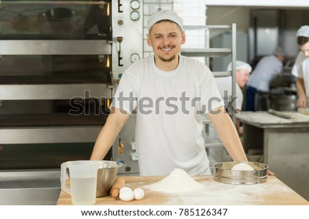 Portrait of a handsome young male baker smiling to the camera posing at his kitchen while working bakery shop store cook chef profession occupation career positivity food nutrition organic qualified