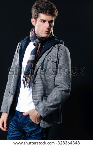 Portrait of a handsome young male with scarf posing â??black background - stock photo