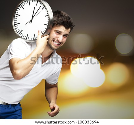 portrait of a handsome young man carrying a clock against an abstract background