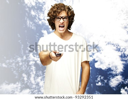 portrait of a handsome young man changing channel against a cloudy sky background - stock photo