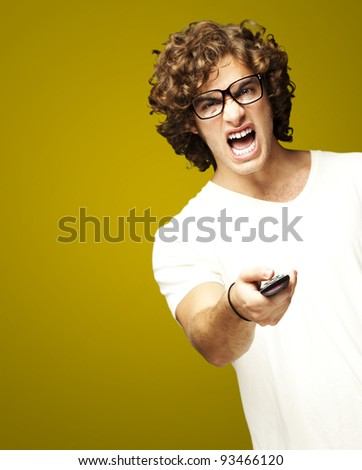 portrait of a handsome young man changing channel against a orange background - stock photo