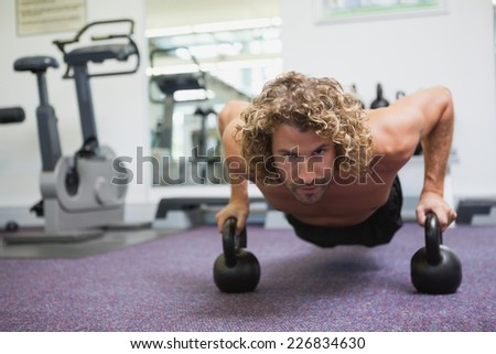 Portrait of a handsome young man doing push ups with kettle bells in gym