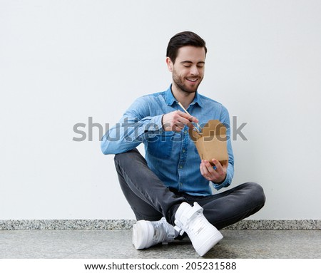 Portrait of a handsome young man eating chinese food with chopsticks  - stock photo