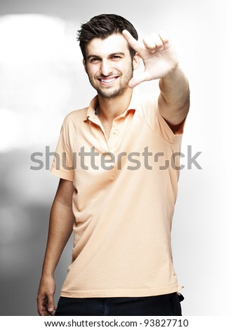 portrait of a handsome young man gesturing indoor - stock photo