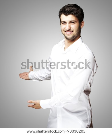 portrait of a handsome young man gesturing welcome over grey
