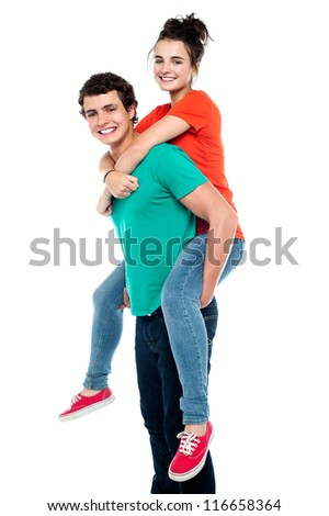 Portrait of a handsome young man giving a piggyback ride to his girlfriend - Indoor - stock photo