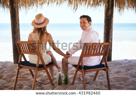 Portrait of a handsome young man holding hands with her wife and enjoying the ocean view during their summer vacation