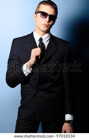 Portrait of a handsome young man in a suit. Shot in a studio. - stock photo