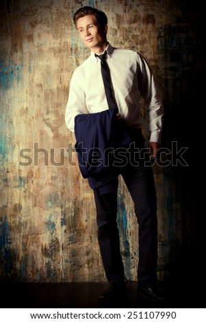 Portrait of a handsome young man in elegant suit standing over grunge background.