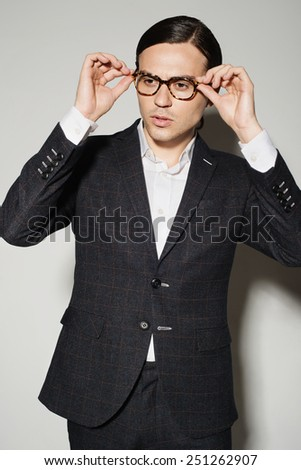 Portrait of a handsome young man in studio on a white background in a suit and glasses
