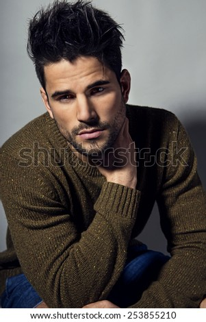 portrait of a handsome young man in sweater posing in studio - stock photo