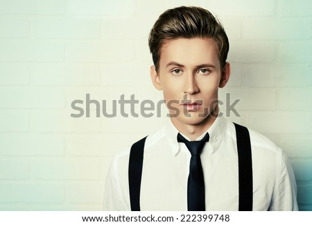 Portrait of a handsome young man in white shirt andblack tie by white brick wall. Business. - stock photo