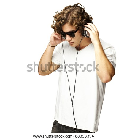 portrait of a handsome young man listening music against a white background