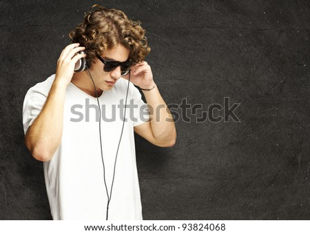 portrait of a handsome young man listening to music against a grunge wall - stock photo