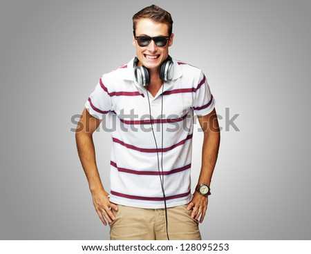 Portrait Of A Handsome Young Man Listening To Music On Gray Background
