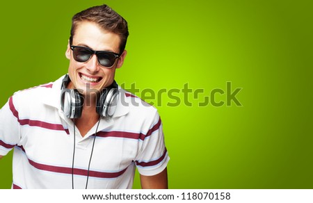 Portrait Of A Handsome Young Man Listening To Music On Green Background