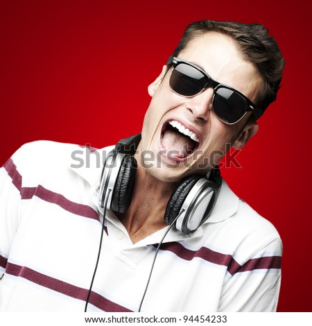 portrait of a handsome young man listening to music over red background - stock photo