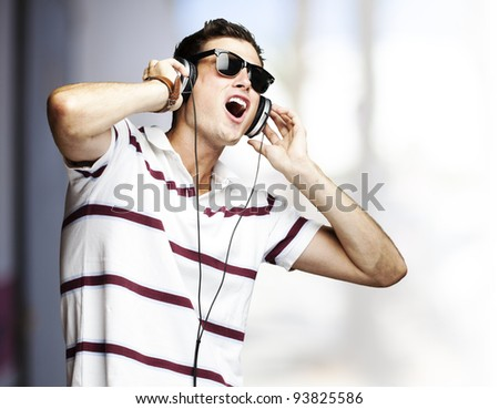 portrait of a handsome young man listening to music with headphones outdoor