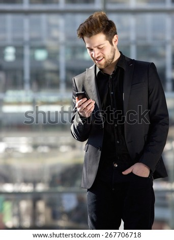 Portrait of a handsome young man looking at mobile phone text message - stock photo