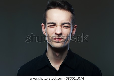 portrait of a handsome young man making a weired face, isolated on gray