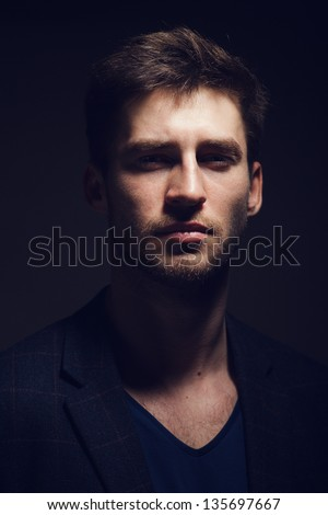 Portrait of a handsome young man on a dark background