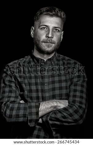 Portrait of a handsome young man on dark background, dramatic lowkey black and white image. - stock photo