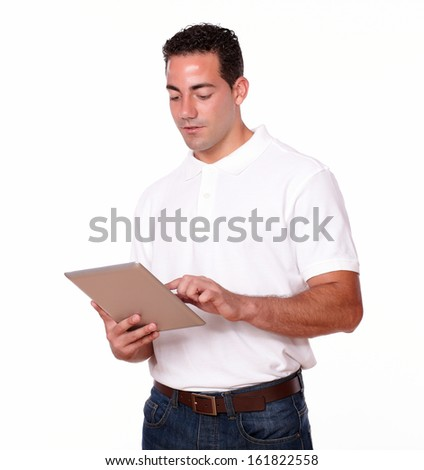 Portrait of a handsome young man on white t-shirt and jeans using his tablet pc on isolated studio