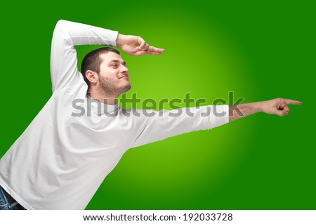 portrait of a handsome young man pointing and joking  - stock photo