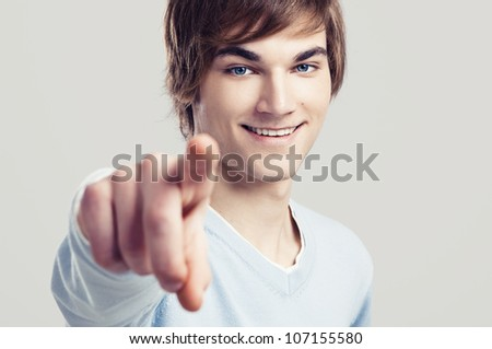 Portrait of a handsome young man pointing, over a gray background - stock photo