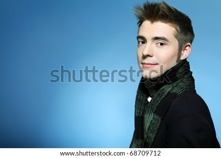 Portrait of a handsome young man posing over grey background.