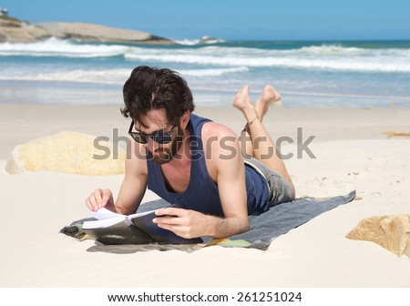 Portrait of a handsome young man reading book at the beach