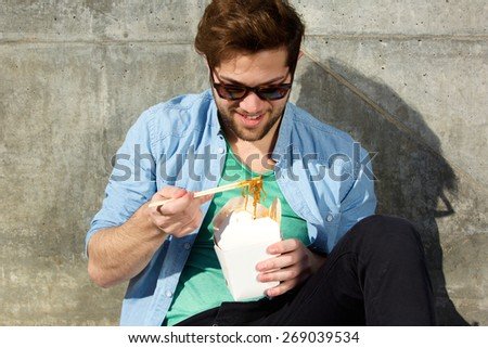 Portrait of a handsome young man relaxing and eating asian food with chopsticks - stock photo
