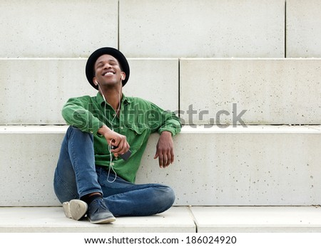 Portrait of a handsome young man relaxing outdoors with earphones - stock photo