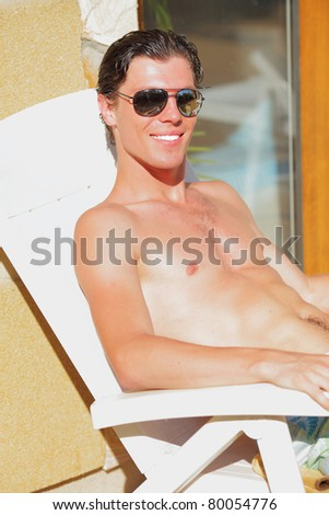 Portrait of a handsome young man resting near a pool
