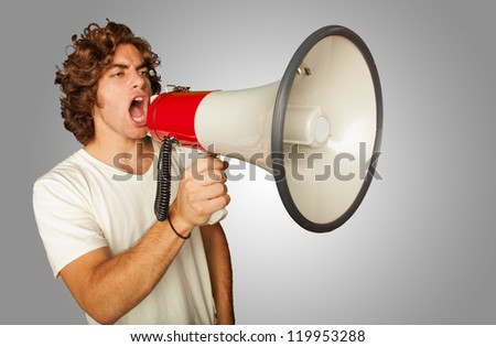 Portrait Of A Handsome Young Man Shouting With Megaphone On Gray Background - stock photo