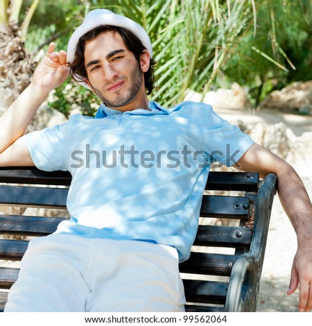 Portrait of a handsome young man sitting in the sun on bench at park