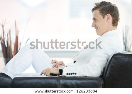 Portrait of a handsome young man sitting on couch indoor - stock photo