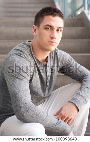 portrait of a handsome young man sitting on the steps inside a building