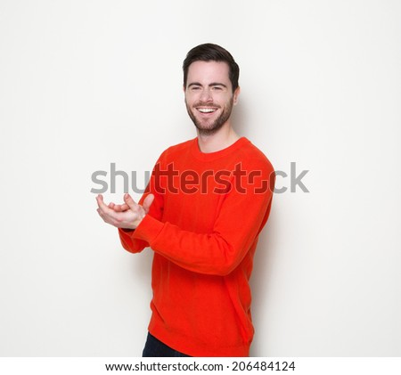 Portrait of a handsome young man smiling and clapping hands - stock photo