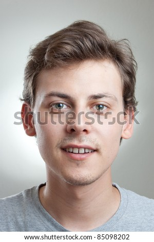 portrait of a handsome young man smiling at camera, isolated on gray - stock photo