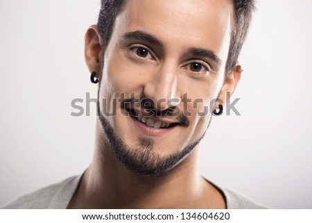 Portrait of a handsome young man smiling, over a gray background - stock photo
