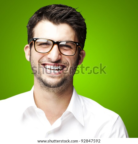 portrait of a handsome young man smiling over green background - stock photo
