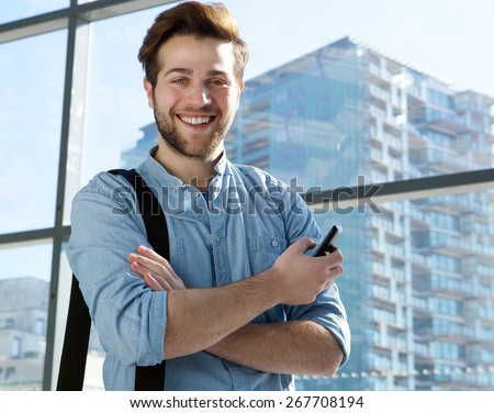 Portrait of a handsome young man smiling with mobile phone - stock photo