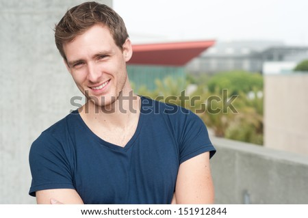 portrait of a handsome young man standing outside - stock photo