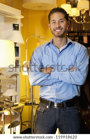 Portrait of a handsome young man standing with arms crossed in lights store