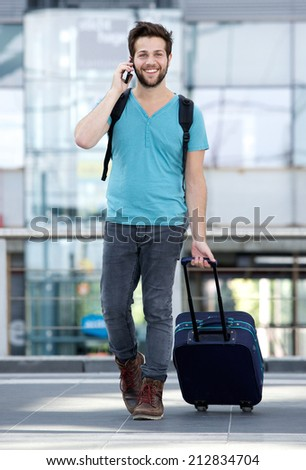 Portrait of a handsome young man talking on mobile phone with bag - stock photo