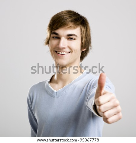 Portrait of a handsome young man thinking, over a gray background - stock photo