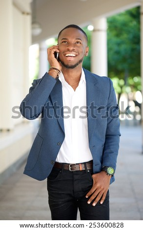 Portrait of a handsome young man walking and talking by mobile phone - stock photo