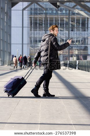 Portrait of a handsome young man walking with bag and mobile phone at station - stock photo